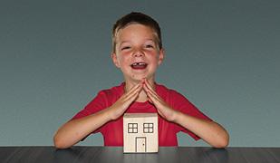 Junge stell mit den Händen das Dach eines kleinen Hauses dar